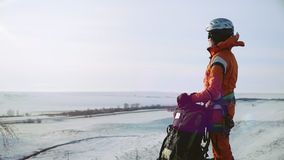 El escalador de la muchacha se coloca en el pico de la montaña, al lado de su mochila y miradas en la distancia en el paisaje almacen de video