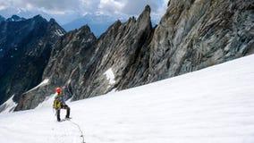 El escalador de montaña masculino toma una rotura en un alto glaciar alpino y mira su manera abajo y la ruta de la pendiente Foto de archivo libre de regalías