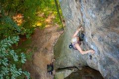 El escalador de roca de la mujer está subiendo en una pared rocosa Imagen de archivo libre de regalías