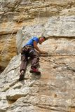 El escalador de roca mira abajo Foto de archivo libre de regalías