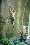 El escalador de roca muscular sube en la pared del acantilado con la cuerda Imagen de archivo libre de regalías