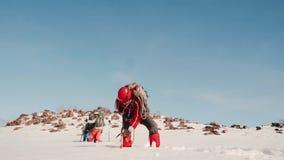El escalador del hombre zafa la cuerda con una carabina del rompehielos pegado en la nieve gruesa en el fondo es un grupo de metrajes