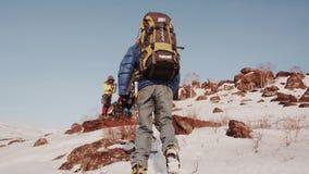 El escalador en las rocas y la nieve sube para arriba la cuesta a sus camaradas en la campaña, que hizo un pequeño alto en almacen de metraje de vídeo