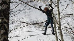 El escalador femenino joven camina por el puente de cuerda pendiente en altas cuerdas cursa en parque extremo Concepto de la esca almacen de video