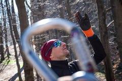El escalador joven está mirando para arriba Visión con el mosquetón fotografía de archivo libre de regalías