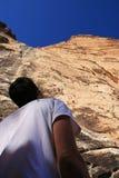 El escalador mira para arriba el acantilado fotografía de archivo libre de regalías