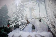 El escaparate de la Navidad con los árboles de navidad y los osos polares artificiales adornados juega en nieve imagenes de archivo