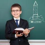 El escolar con el libro, dibujo del lanzamiento del cohete de espacio en fondo de la pizarra, se vistió en el traje negro clásico Foto de archivo libre de regalías