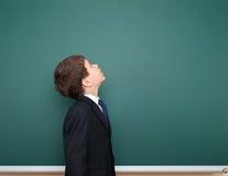 El escolar en traje negro mira para arriba en el fondo verde de la pizarra, concepto de la educación Fotografía de archivo