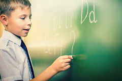 El escolar escribe alfabeto inglés con tiza en la pizarra Fotos de archivo libres de regalías