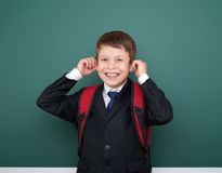 El escolar hace caras en traje negro en el fondo verde con la mochila roja, concepto de la pizarra de la educación Fotos de archivo libres de regalías