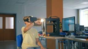 El escolar primario utiliza los vidrios de la realidad virtual durante clase de informática almacen de metraje de vídeo