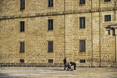 El Escorial Monastery and young family. El Escorial, November 2012. Royal Seat and Monastery of San Lorenzo de El Escorial, residence of some kings of Spain and Royalty Free Stock Photos