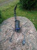 El escorpión del metal se está sentando en una piedra Foto de archivo
