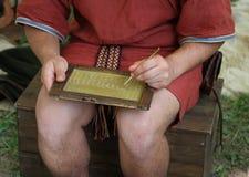 El ESCRIBANO joven escribe en una tableta de cera Imagen de archivo