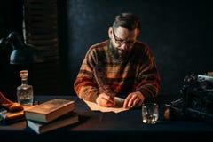 El escritor barbudo en vidrios escribe con una pluma fotos de archivo