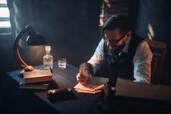 El escritor barbudo en vidrios escribe con una pluma fotografía de archivo libre de regalías