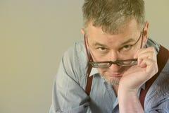 El escritor con los vidrios y las ligas está pensando en su trabajo Imágenes de archivo libres de regalías