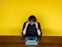 El escritor del hombre en camisa y vidrios negros, se coloca con su cabeza aplicada en una máquina de escribir en una tabla sobre foto de archivo libre de regalías