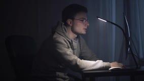 El escritor joven agotado despierta delante del ordenador en la noche almacen de metraje de vídeo