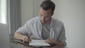 El escritor joven que se sentaba en la tabla que corregía su ensayo escribió en el papel usando negro y pluma del oro y el mostra almacen de video
