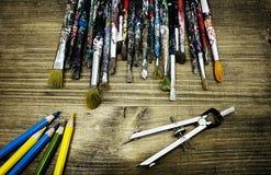 El escritorio de Aritst con las brochas viejas y los lápices coloreados Fotos de archivo