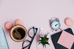 El escritorio de la mujer en la libreta rosada de los vidrios que golpea los lápices con el pie planta macaroo Foto de archivo libre de regalías