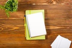 El escritorio de la tabla de la oficina con el sistema de fuentes coloridas, cuaderno de notas en blanco blanco, taza, pluma, PC, Foto de archivo