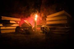 El escritorio del mago Un escritorio encendido por la luz de la vela Un cráneo humano, los libros viejos en la arena emerge Fondo Foto de archivo libre de regalías