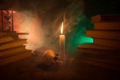 El escritorio del mago Un escritorio encendido por la luz de la vela Un cráneo humano, los libros viejos en la arena emerge Fondo Imagen de archivo libre de regalías