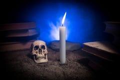 El escritorio del mago Un escritorio encendido por la luz de la vela Un cráneo humano, los libros viejos en la arena emerge Fondo Imágenes de archivo libres de regalías