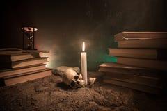 El escritorio del mago Un escritorio encendido por la luz de la vela Un cráneo humano, los libros viejos en la arena emerge Fondo Fotos de archivo libres de regalías