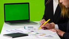 El escritorio del trabajo en la oficina, el hombre y la mujer dibujan un gráfico, cuaderno abierto con la pantalla verde metrajes