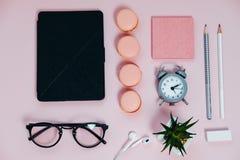 El escritorio femenino en la libreta rosada de los vidrios que golpea los lápices con el pie planta macaro Fotos de archivo libres de regalías