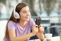 El escuchar adolescente feliz la música en una cafetería Imagenes de archivo
