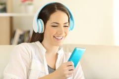 El escuchar adolescente feliz la música usando un smartphone azul Foto de archivo libre de regalías