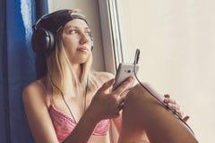 El escuchar adolescente feliz la música y mirada a través de la ventana Foto de archivo