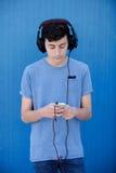 El escuchar adolescente la música con los auriculares Foto de archivo libre de regalías