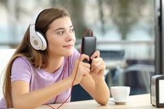 El escuchar adolescente la música en una terraza de la barra Fotos de archivo