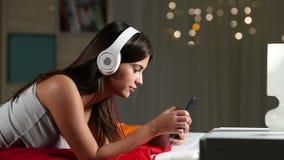 El escuchar adolescente la música que se relaja en una cama