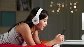 El escuchar adolescente la música y canto en una cama