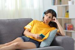 El escuchar adolescente serio la música en línea en casa Foto de archivo