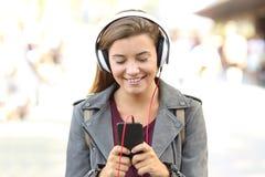 El escuchar adolescente sonriente la música en un teléfono elegante Fotos de archivo