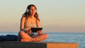 El escuchar de relajación adolescente para enfriar hacia fuera música en la puesta del sol almacen de video