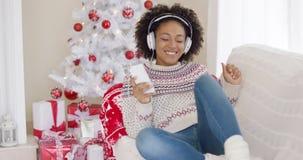 El escuchar de relajación de la chica joven la música de la Navidad almacen de metraje de vídeo