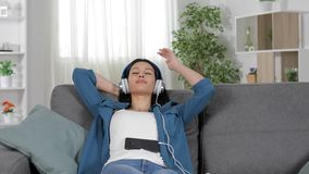 El escuchar de relajación de la mujer la música en un sofá almacen de metraje de vídeo