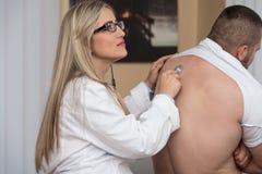 El escuchar detrás del paciente con el estetoscopio imágenes de archivo libres de regalías
