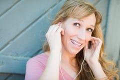 El escuchar femenino adolescente expresivo la música con los auriculares Foto de archivo