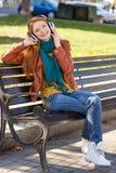 El escuchar femenino contento alegre joven la música en el parque Foto de archivo