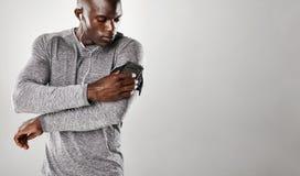 El escuchar masculino africano la música en el teléfono móvil fotografía de archivo
